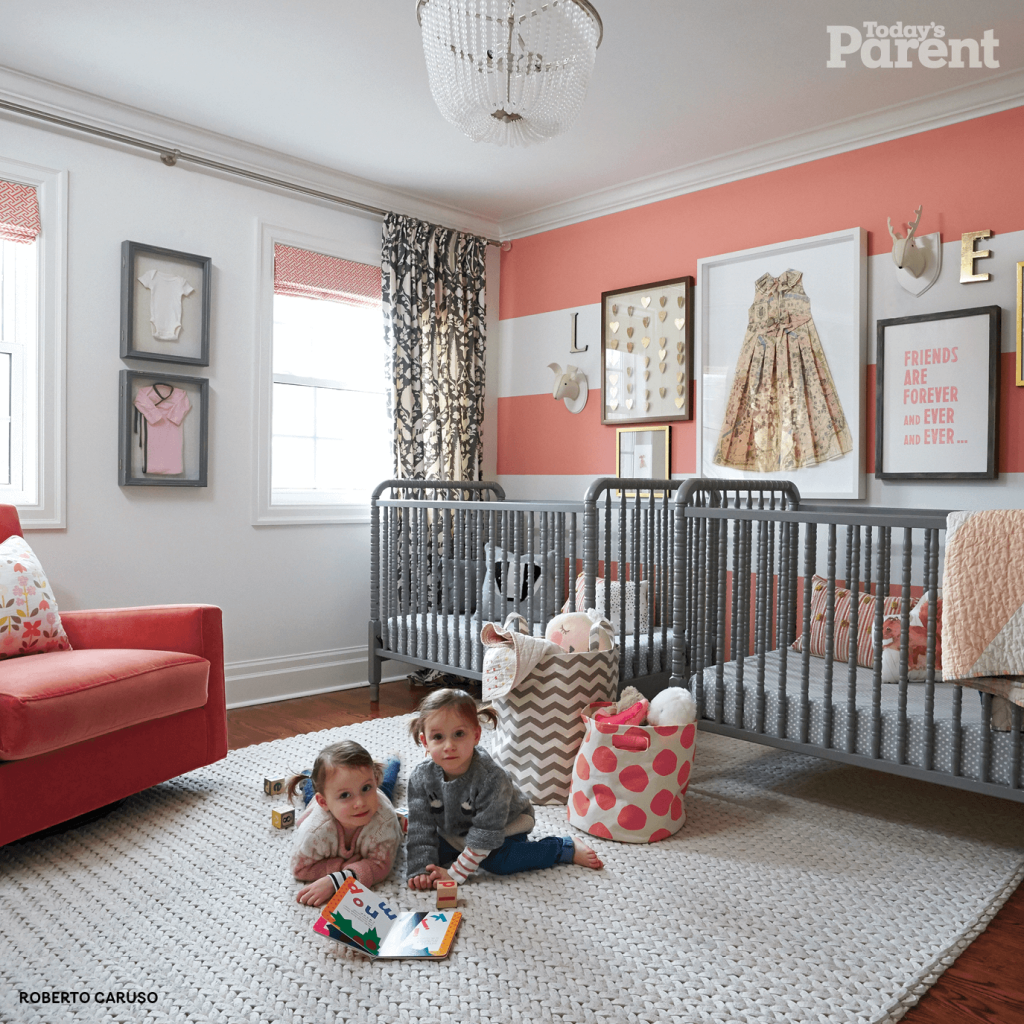 Twin room with gray cribs and two twin girls on the floor of the room.