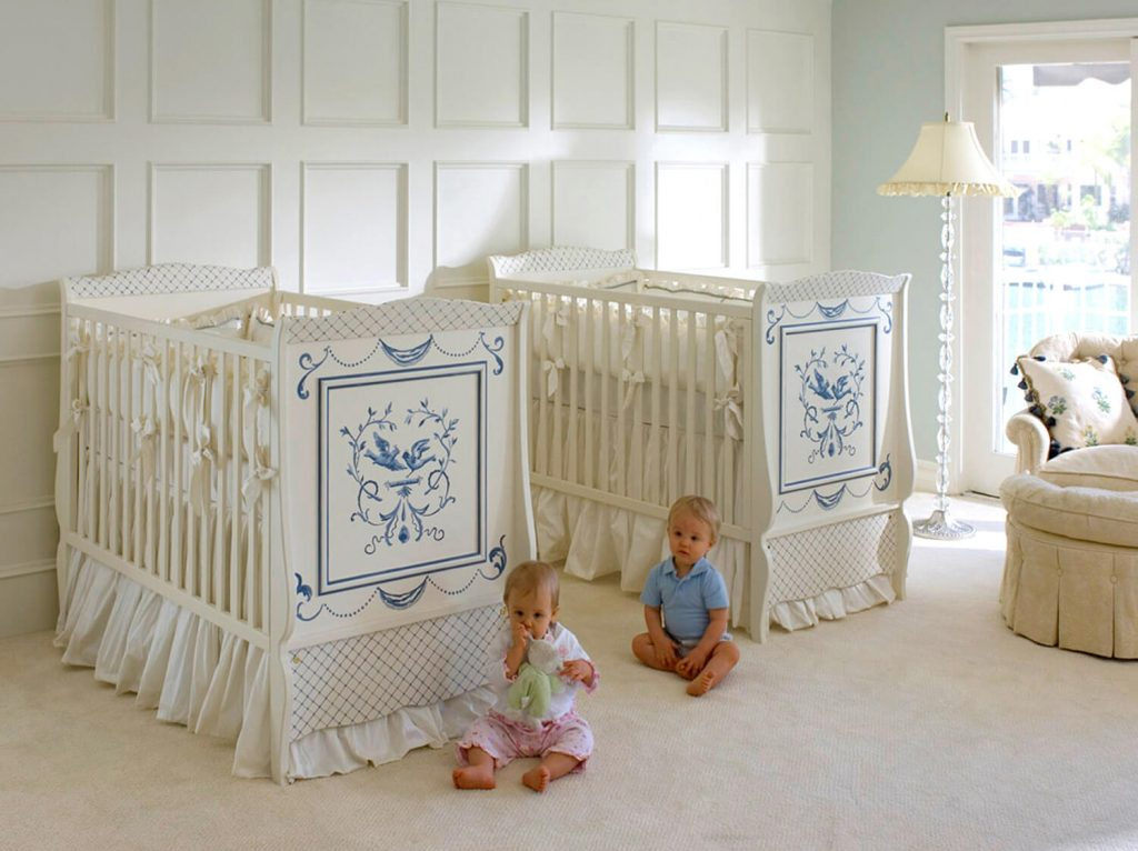 Fancy looking gender neutral twin nursery with boy girl twins sitting on the floor in front of cribs.