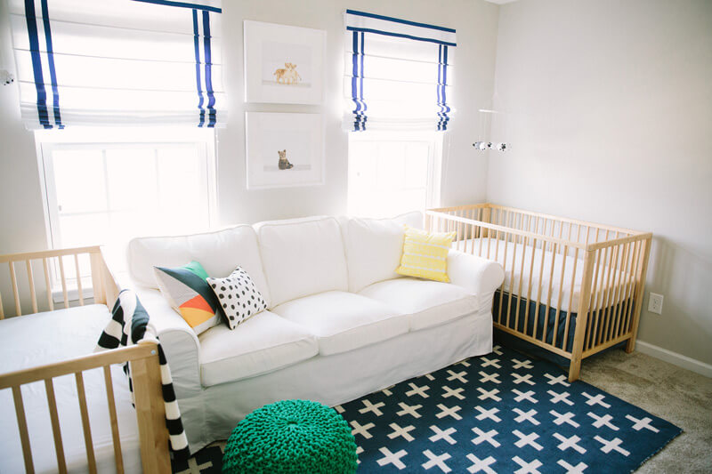 Gender neutral twin nursery with natural wood cribs and navy rug
