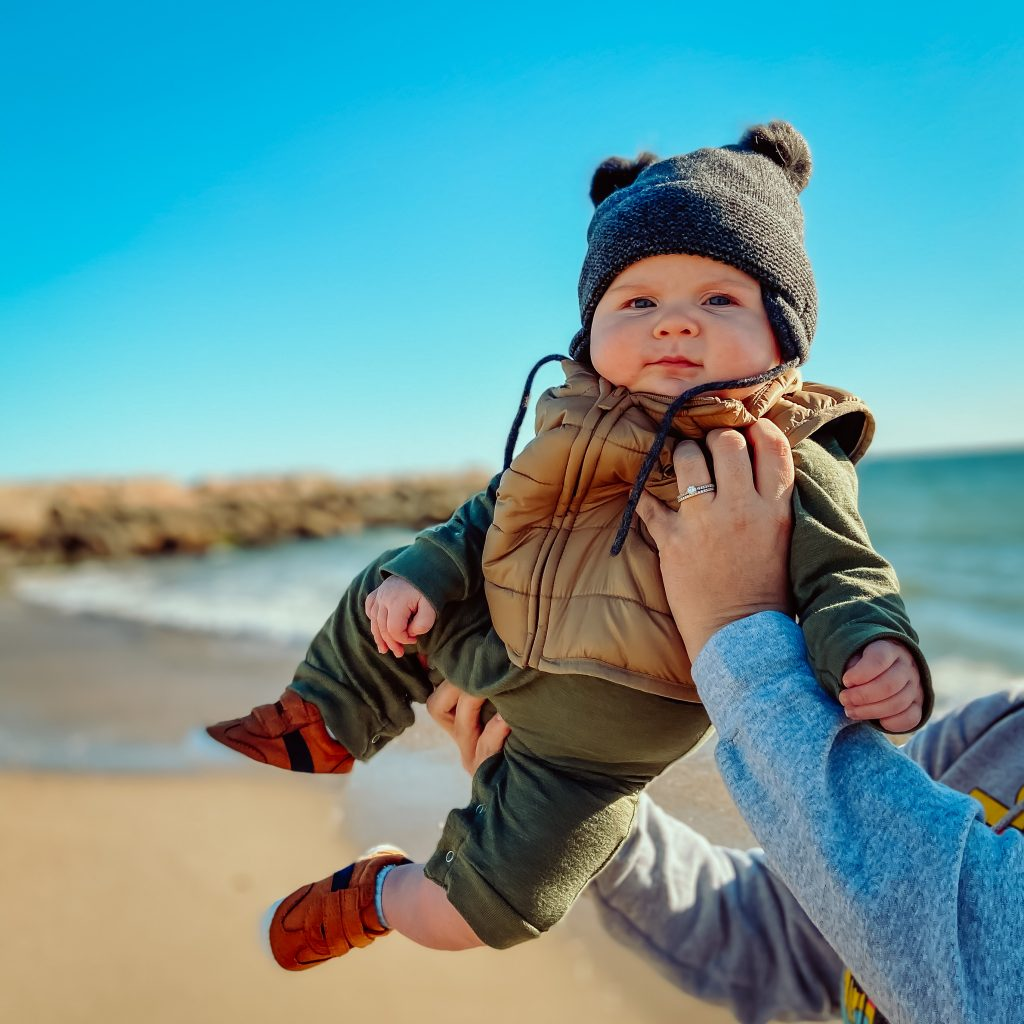 6 month old baby being held up in front of the ocean