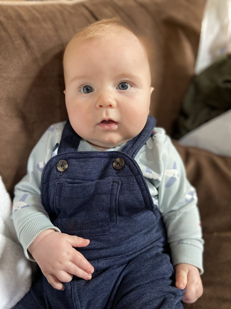6 month old baby boy wearing blue overalls sitting on the couch